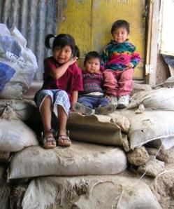 Tres niños sentados en sacos de arena