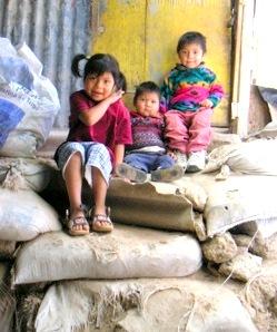 Three children sitting on several large sandbags