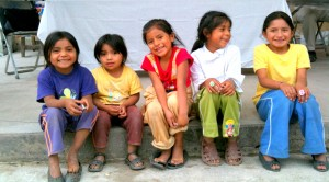 Five smiling children sitting on a step.
